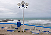 Old man, pensioner looking out to sea, Historical, old fishing village, Ericeira, Portugal, Atlantic