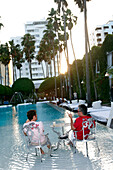 Two men relaxing at the Delano Hotel pool at sunset, South Beach, Miami Beach, Florida, USA