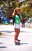 Young woman skateboarding at Lummus Park, South Beach, Miami Beach, Florida, USA