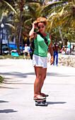 Young woman skateboarding at Lummus Park, South Beach, Miami Beach, Florida, USA