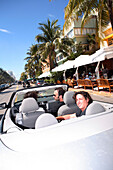 Three men driving a cabriolet on Ocean Drive, South Beach, Miami Beach, Florida, USA