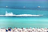 People on the beach watching a motor boat racing, South Beach, Miami Beach, Florida, USA
