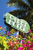 Cadet Hotel neon sign above blooming flowers at daytime, South Beach, Miami Beach, Florida, USA