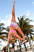 Gymnast on parallel bars at Lummus Park, South Beach, Miami Beach, Florida, USA