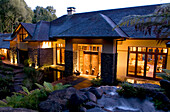 View at the illuminated windows at the Treetops Lodge in the evening, North Island, New Zealand, Oceania