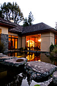 View over a pond at the illuminated windows at the Treetops Lodge in the evening, North Island, New Zealand, Oceania