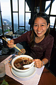 Laughing woman eating at a restaurant at Chiufen, Taiwan, Asia