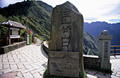 a stone with characters at the beginning of the climb to Yushan mountain at Yushan National Park, Taiwan, Asia