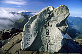 Stone with characters on the main peak of Yushan mountains in the sunlight, Yushan National Park, Taiwan, Asia