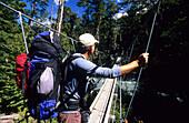 Man on a suspension bridge above the Rees Dart River, Mount Aspiring National Park, South Island, New Zealand, Oceania