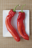 Close up, Close-up, Closeup, Color, Colour, Detail, Details, Dish, Dishes, Food, Foodstuff, Healthy, Healthy food, Indoor, Indoors, Interior, Nourishment, Pair, Pepper, Peppers, Plate, Plates, Raw, Red, Red pepper, Red peppers, Still life, Two, Veg, Veget