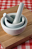 2 mortars and pestles on cutting board, on red checkered table cloth