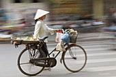 Woman street vendor pushing a bicycle, Hanoi, Vietnam