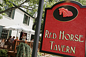 Washington Street, Red Horse Tavern, table, umbrella, alfresco dining, red sign. Middleburg. Virginia. USA.