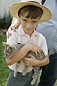 Amish Farm Tour, boy, kitten, straw hat. Shipshewana. Indiana. USA.