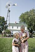 Amish Farm Tour, girls, sisters, cat, kitten, house, windmill. Shipshewana. Indiana. USA.