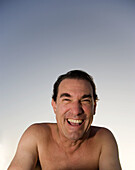 Man with no shirt looking at camera laughing outdoors, Hollywood, Florida, USA