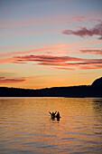 Kayakers enjoying a sunset on the water in simlik bay. Washington.  NW USA