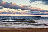 Morning skies over waves crashing on beach of Agawa Bay in Lake Superior, Canada