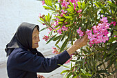 An elderly lady pruning a flower bush at the fishing town of Githeo, Greece.