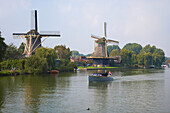 A motorboat on the river Vecht driving past two windmills, Weesp, Netherlands, Europe