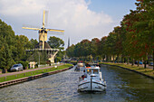 A houseboat on the river Smal Weesp driving past a windmill, Weesp, Netherlands, Europe