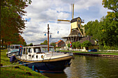 Windmill and houseboat at teh banks of the river Smal Weesp under cloudy sky, Weesp, Netherlands, Europe