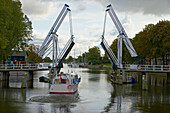 A motorboat on the river Vecht driving past a bascule bridge, Netherlands, Europe
