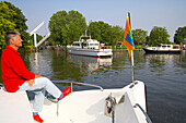 A man sitting on the bow of a boat, boats driving on the river Vecht, Netherlands, Europe