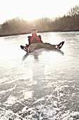 Ice skater sitting on ice, lake Ammersee, Upper Bavaria, Germany