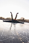 Ice skater lying on ice, Lake Ammersee, Upper Bavaria, Germany