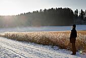 Senior man watching winter scenery, Windach, Upper Bavaria, Germany