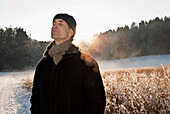 Senior man with closed eyes standing in winter scenery, Windach, Upper Bavaria, Germany