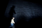 Person walking past a wall at night, Oslo, Norway