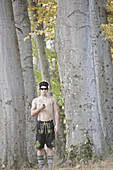 Young man wearing leather trousers standing in a forest, Kaufbeuren, Bavaria, Germany