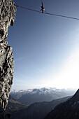Mann balanciert auf einem Seil über einem Abgrund, Slackline in den Bergen, Oberstdorf, Bayern, Deutschland