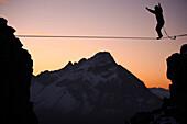 Mann balanciert auf einem Seil im Abendrot, Slackline in den Bergen, Oberstdorf, Bayern, Deutschland