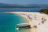 An excursion boat and people at the beach at the Golden Horn, Bol, Brac Island, Dalmatia, Croatia, Europe