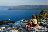 Mother and child sitting on rocks in the sunset light, Vidovica, Vidova Gora, Brac Island, Dalmatia, Croatia, Europe