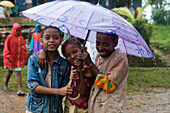 It's raining and we don't care! Happy children in the rain, Ambodifototra, Nosy St. Marie, Madagascar, Africa