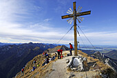 Hikers near summit cross of Klammspitze, Ammergau Alps, Pfaffenwinkel, Bavaria, Germany