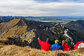 Hikers enjoying view over Ammergau Alps, lake Forggensee in background, Klammspitze, Ammergau Alps, Pfaffenwinkel, Bavaria, Germany