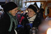 Two young women visiting Christmas market, Frauenchiemsee, Chiemgau, Bavaria, Germany
