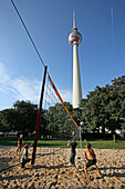 volleyball game below television tower near Alexanderplatz, Berlin, capital, Germany