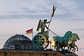 Quadriga, horse and chariot sculpture on Brandenburg Gate, in the background the Reichstag, Berlin