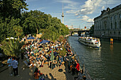 People relaxing at the bank of the river Spree in the sunlight,  Museum Island, Berlin, Germany, Europe