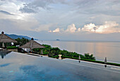The deserted infinity pool at the Amankila Resort under clouded sky, Candi Dasa, Eastern Bali, Indonesia, Asia