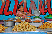 Mature woman preparing food at a snack, Pura Samun Tiga, Bali, Indonesia, Asia