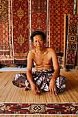 A man and fabric in a shop at Tenganan, Bali Aga village, East Bali, Indonesia, Asia