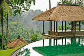 The pool and pavilions of the Amandari Resort in the rain, Yeh Agung valley, Bali, Indonesia, Asia